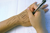 Close-up of a girl writing on her hand with a pen