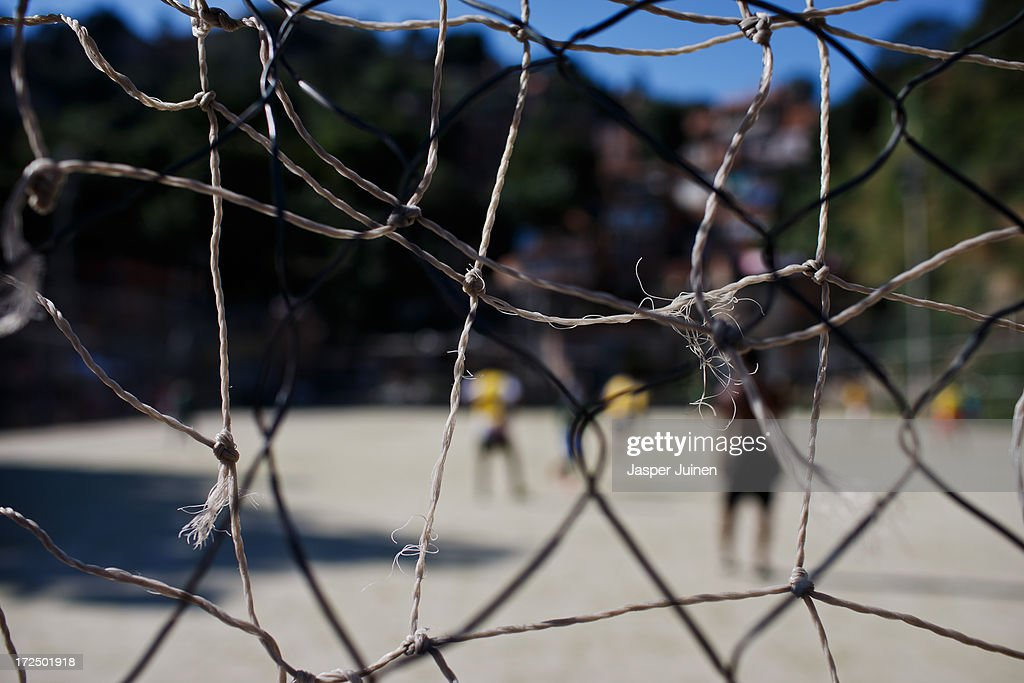 A close-up of a goalnet on a football pitch during a game of football at the Complexo do Alemao favela on June 29, 2013 in Rio de Janeiro, Brazil. It was at the end of 2010 that under the stage of pacification some 300 police officers went into the Complexo do Alemao with tanks and helicopters to drive out the criminal gangs to establish a permanent police presences and to set up social services such as schools, healthcare centers, and rubbish collection. The Complexo do Alemao favela is, with a population of 100, 000 and stretching for more than 3 kilometers with a maze of narrow alleys and stairways, one of the largest favelas in Rio de Janeiro.