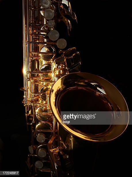 Close-up of a golden saxophone on a black background
