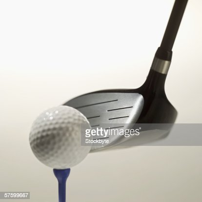 close-up of a golf club, a golf ball and a tee