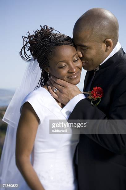 Close-up of a groom kissing his bride