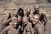 Close-up of a group of people covered with mud smiling