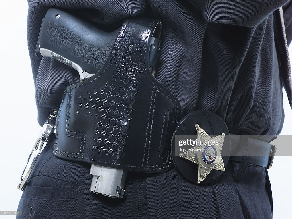 a closeup of a gun police badge and handcuffs on a police officers