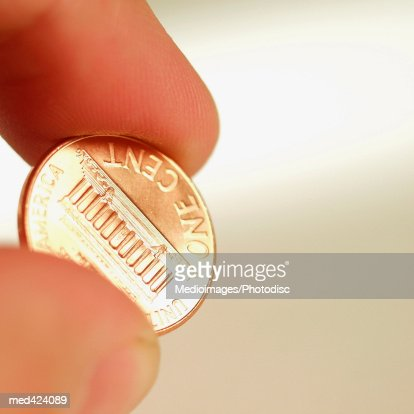 Close-up of a hand holding a one cent coin