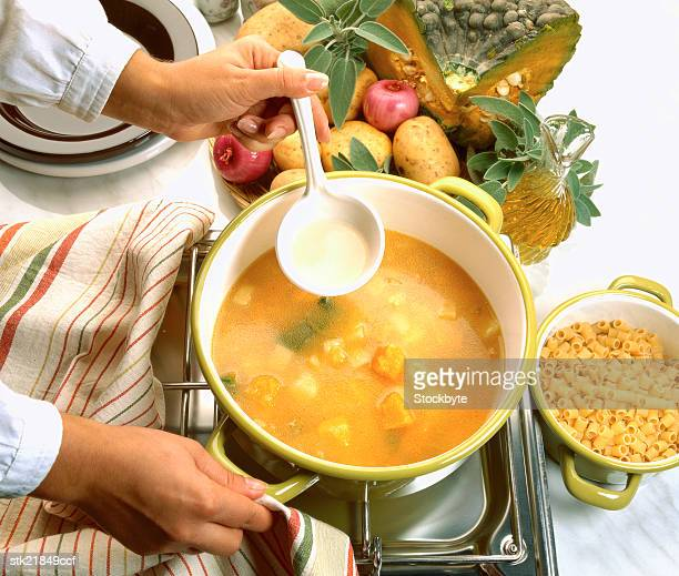close-up of a hand stirring a bowl of soup cooking on a stove