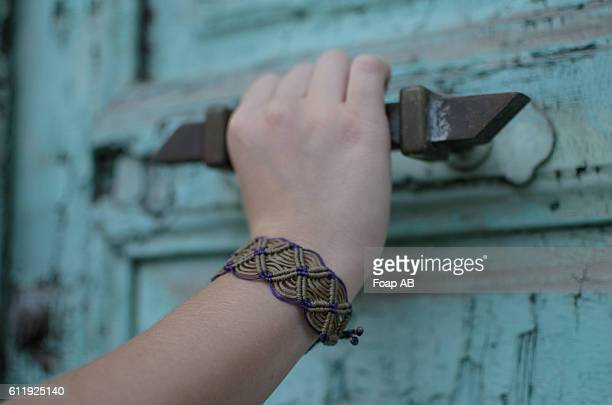 Close-up of a hand with bracelet holding door handle