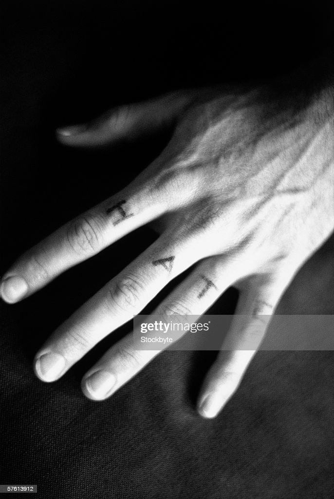 Close-up of a hand with the word hate tattooed on the fingers (black and white) : Stock Photo
