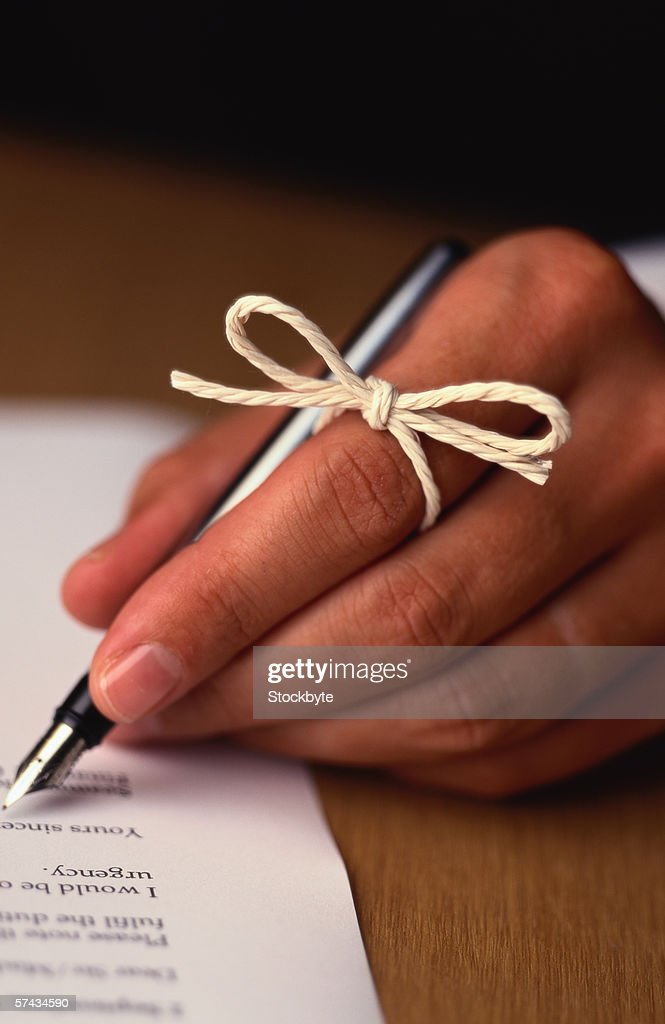 close-up of a hand writing on paper with a string bow on the index finger : Stock Photo