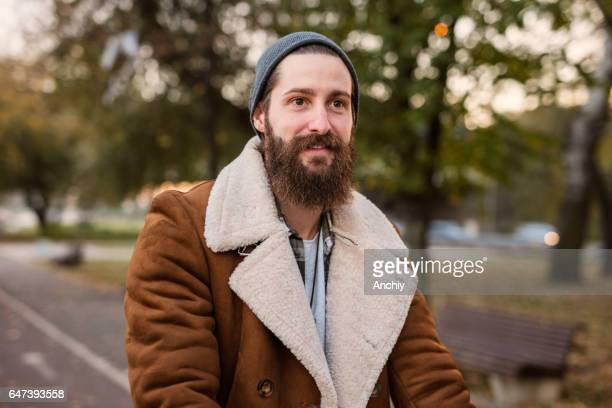 close-up of a handsome bearded hipster in warm clothing on a autumn day