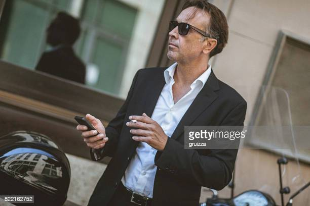 Close-up of a handsome, mature man using smart phone on the city street