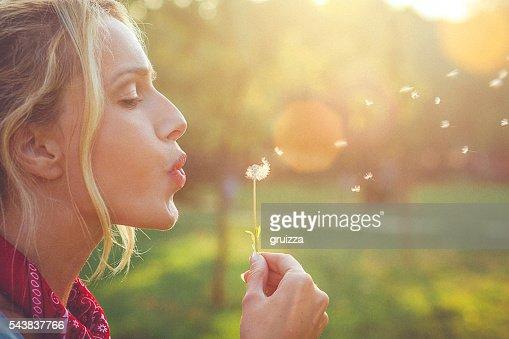 Nahaufnahme eines glückliche junge blondine Frau Blasen Löwenzahn