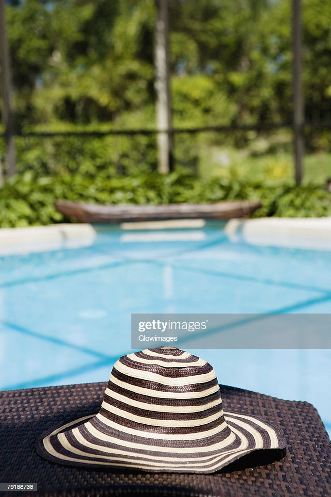 Close-up of a hat on a lounge chair at the poolside : Foto de stock