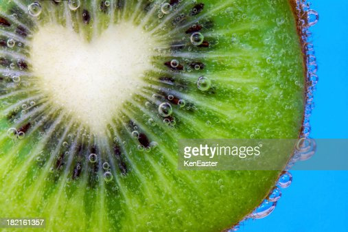 Closeup of a heart shaped kiwi slice in water bubbles : Stock Photo
