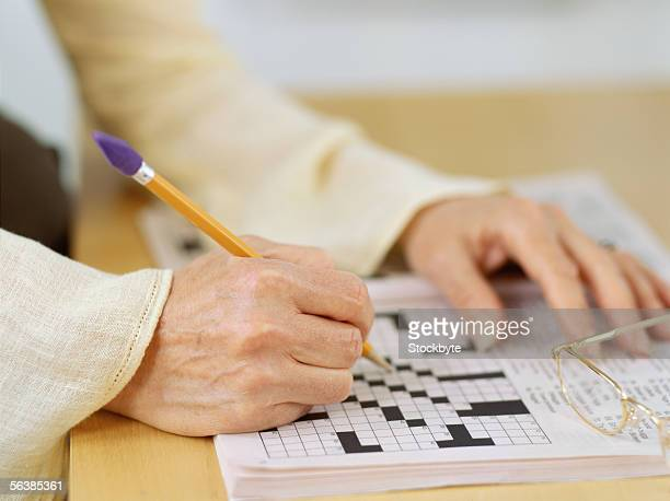 close-up of a human hand doing a crossword puzzle