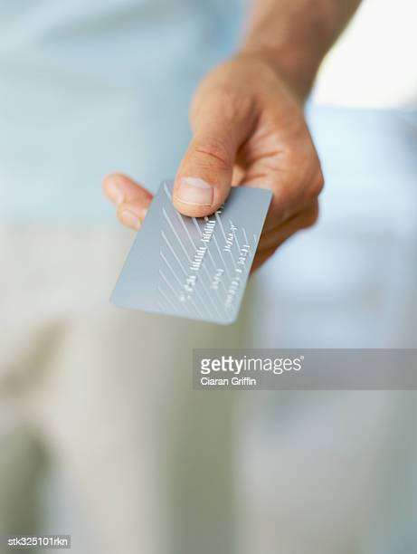 close-up of a human hand holding a credit card