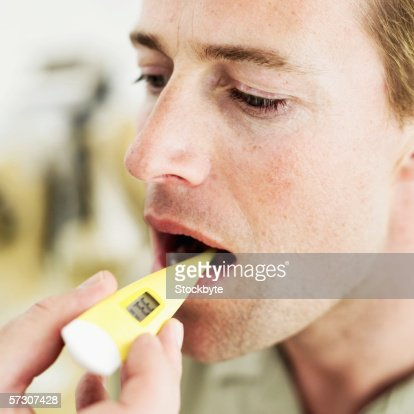 Close-up of a human hand inserting a digital thermometer into a man's mouth