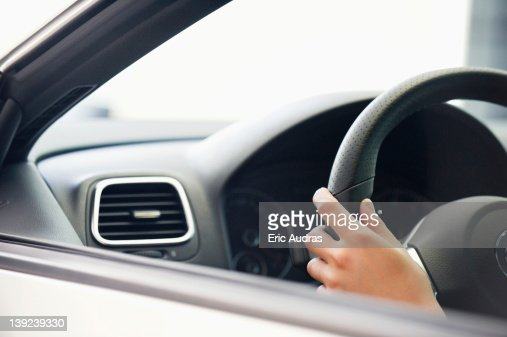 Close-up of a human hand on car steering wheel