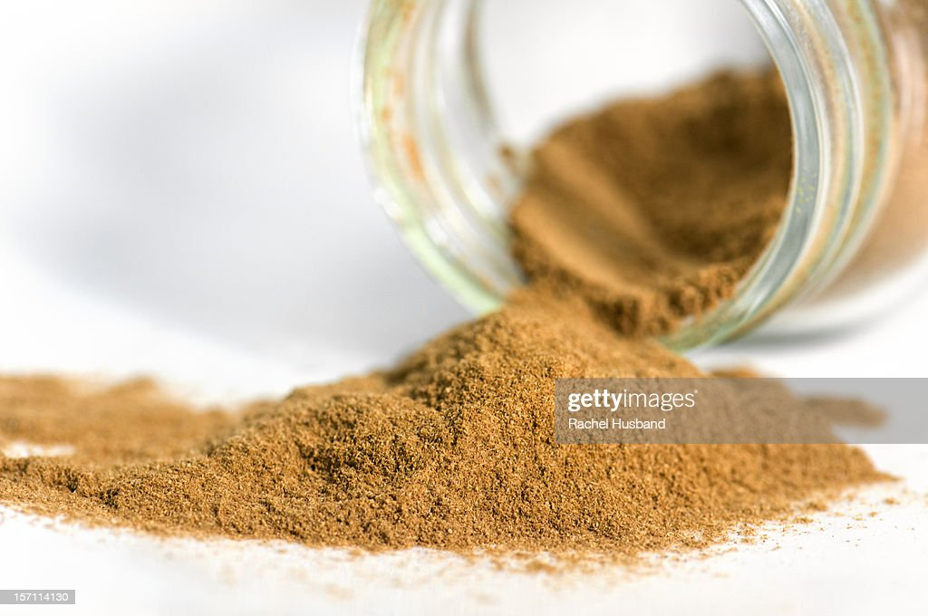 Close-up of a jar of overflowing ground cinnamon : Stock Photo