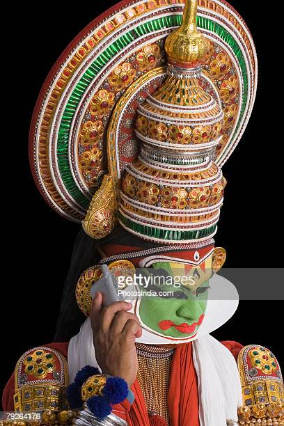 Close-up of a Kathakali dance performer talking on a mobile phone