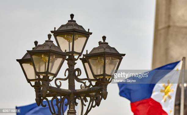 Close-Up Of A Lamp Post And Philippine Flags Against Clear Sky