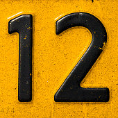 number 12 on a dirty yellow plate