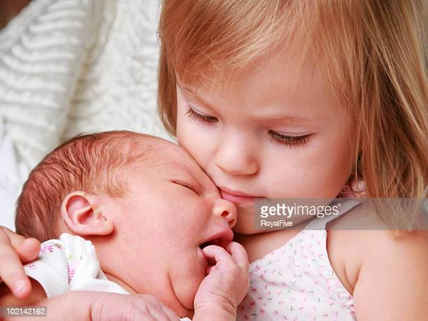 Close-up of a little girl holding her baby sister