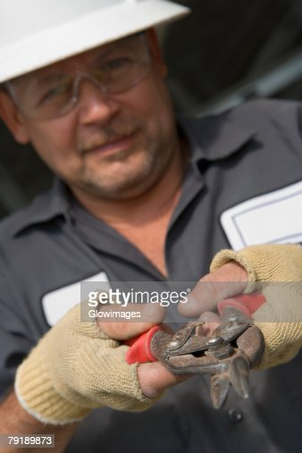 Close-up of a male construction worker holding a cutting tool : Stock Photo
