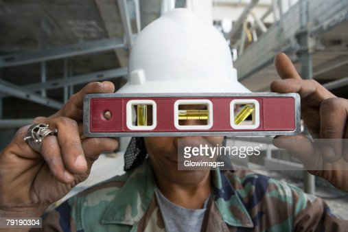 Close-up of a male construction worker holding a level : Stock Photo