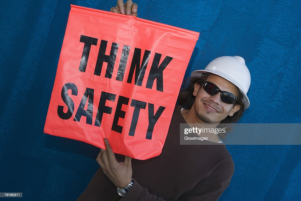 Close-up of a male construction worker smiling and holding a warning sign : Foto de stock