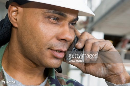 Close-up of a male construction worker talking on a mobile phone : Foto de stock