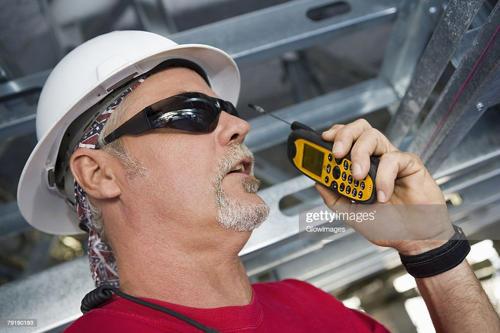 Close-up of a male construction worker talking on a walkie-talkie : Foto de stock