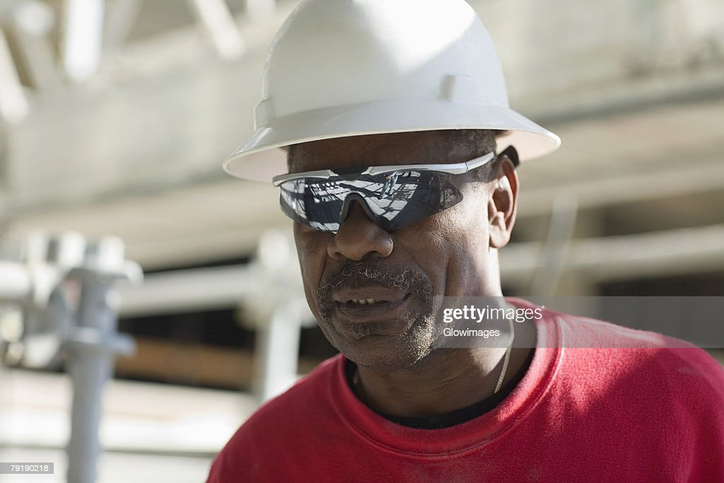 Close-up of a male construction worker with a hardhat and a pair of sunglasses : Foto de stock