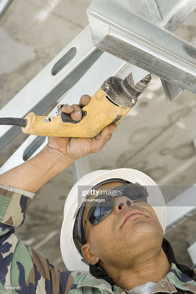 Close-up of a male construction worker working with a hand drill : Stock Photo