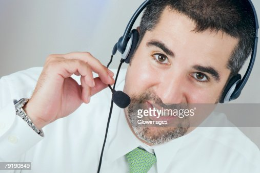 Close-up of a male customer service representative wearing a headset : Stock Photo