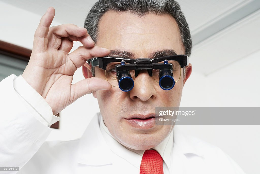 Close-up of a male doctor adjusting lupa binoculars : Stock Photo