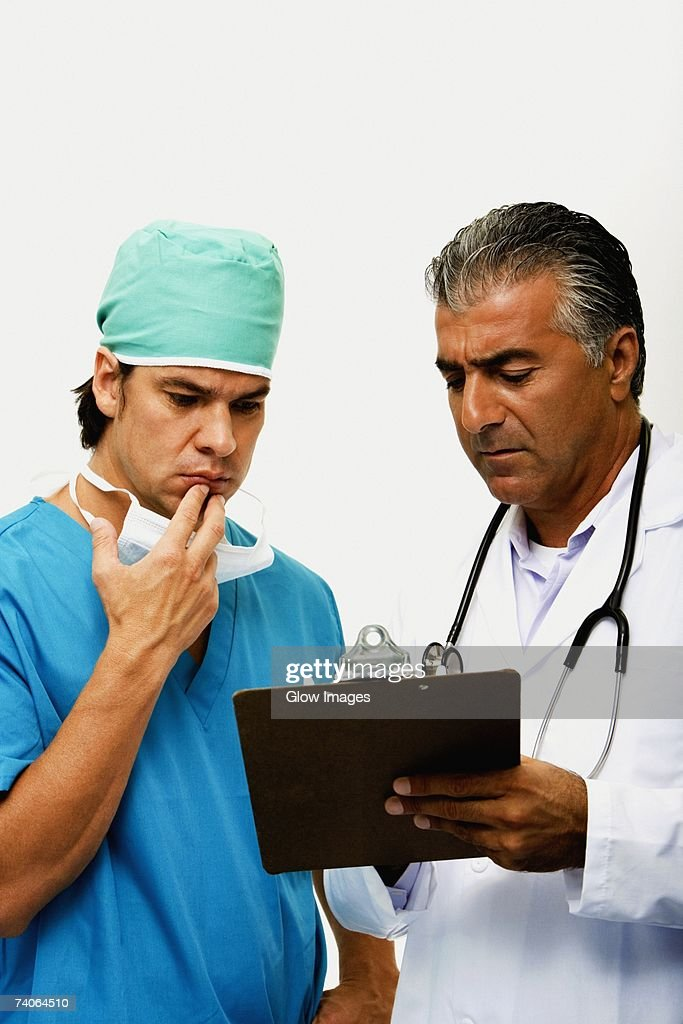 Close-up of a male doctor discussing a report with a surgeon : Stock Photo