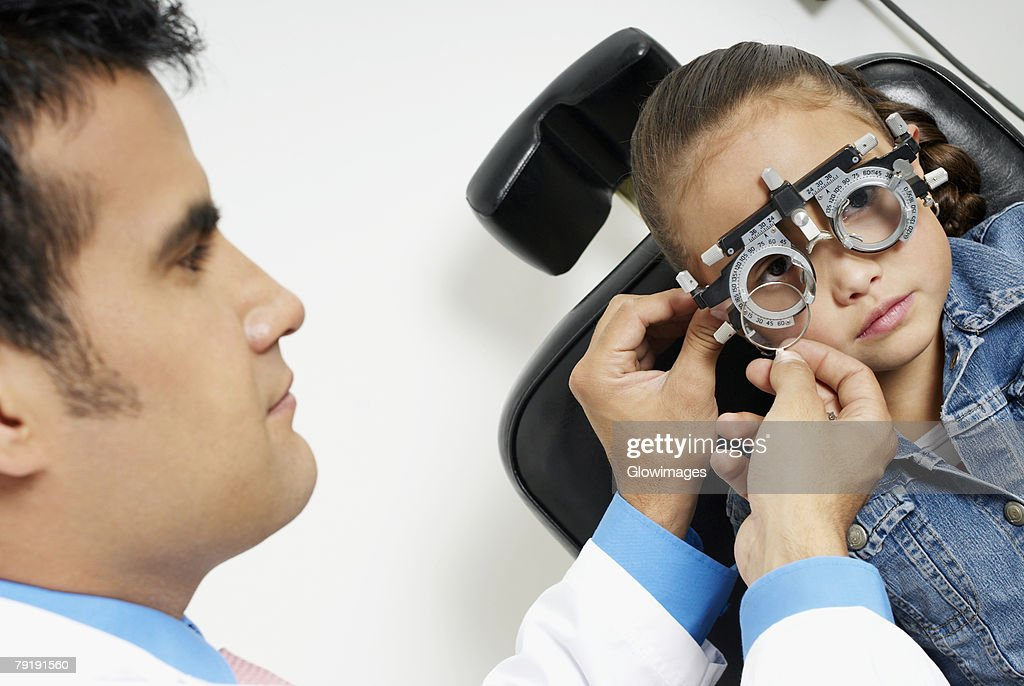 Close-up of a male doctor examining a girl's eye : Stock Photo