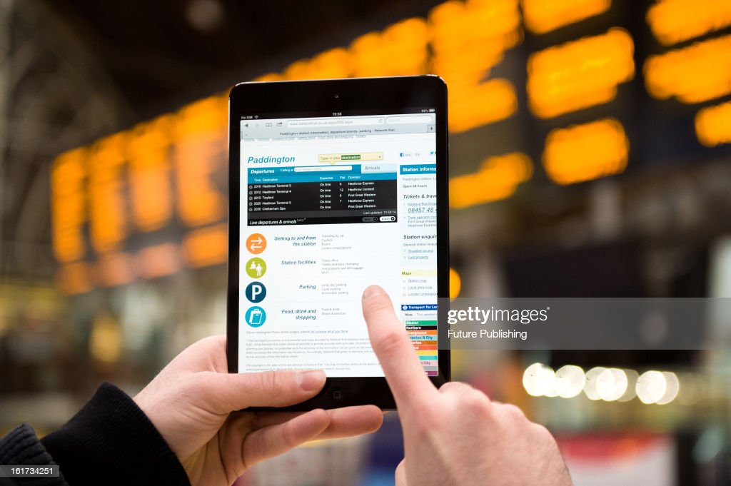A close-up of a man accessing Network Rail's website on an Apple iPad Mini tablet computer at London's Paddington Station on January 14, 2013.