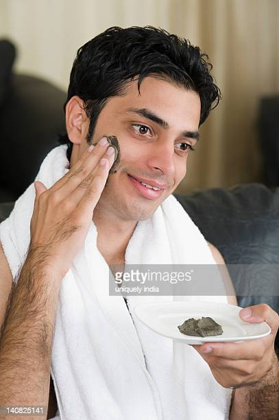 Close-up of a man applying mud pack on his face