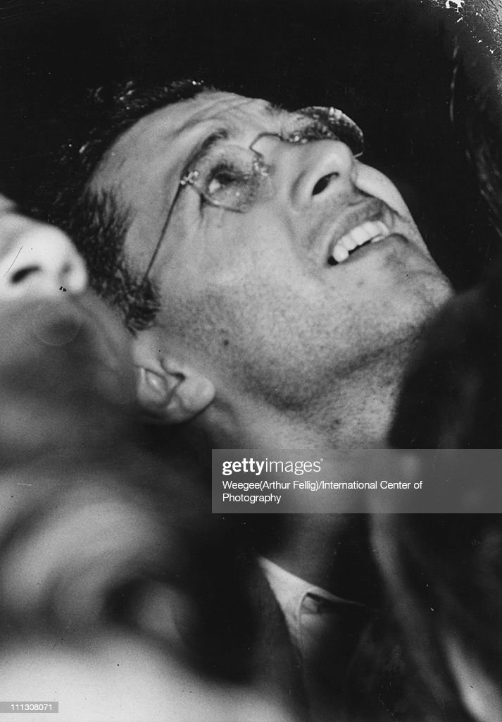 Close-up of a man as he looks up at the Empire State Building where a plane (a North American Aviation B-25 Mitchell bomber) had crashed into the building between the 78th and 80th floors, New York, New York, July 28, 1945. The crash killed 14 people, and it (and the resulting fire) caused over a million dollars worth of damage. (Photo by Weegee(Arthur Fellig)/International Center of Photography/Getty Images)
