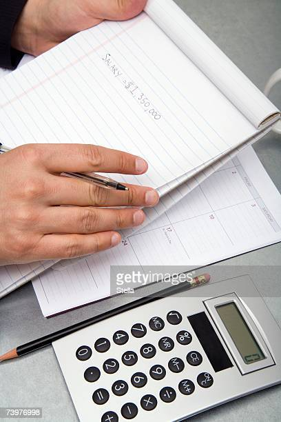 Close-up of a man at a desk with a notepad, pen, diary, calculator, and a pencil