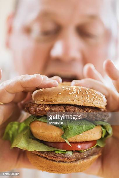 Close-up of a man biting big hamburger.