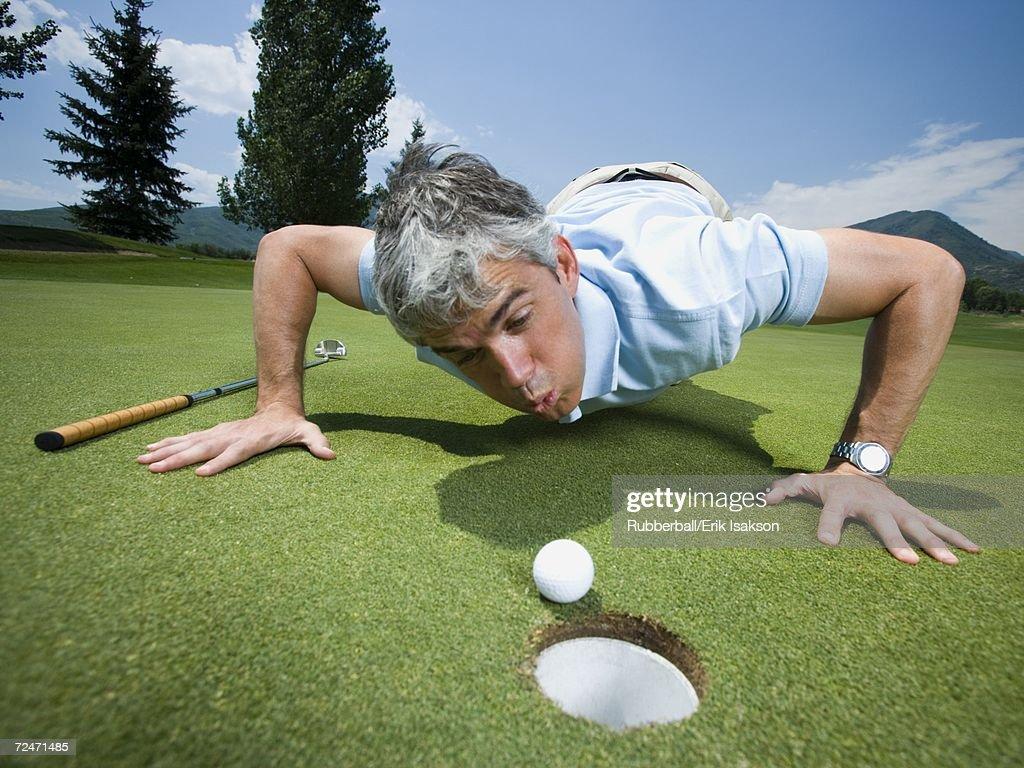 closeup of a man blowing a golf ball towards a hole stock photo