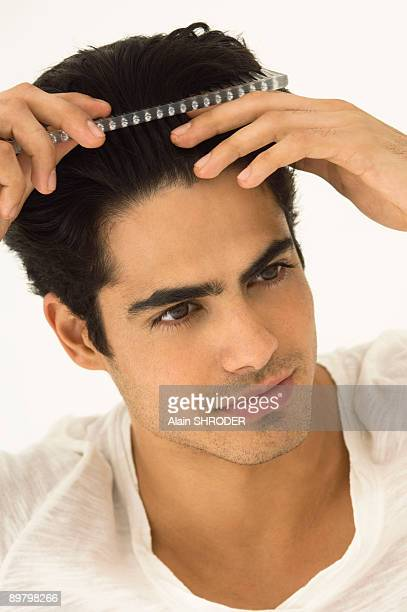 Close-up of a man combing his hair
