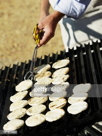 Close-up of a man cooking on a barbeque grill : Foto de stock