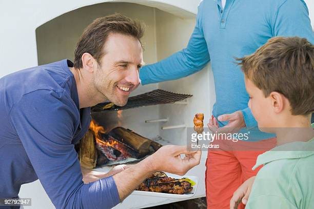 Close-up of a man giving roasted kebab to his son