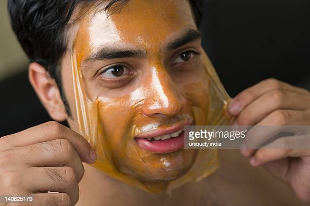 Close-up of a man peeling off facial mask from face