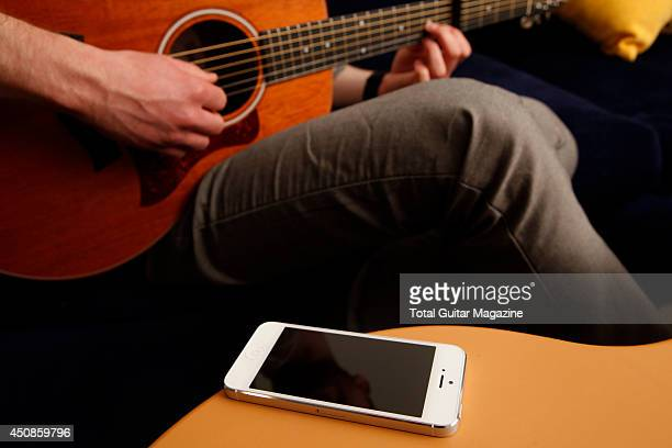 A closeup of a man playing a Taylor acoustic guitar alongside an Apple iPhone 5 smartphone photographed during a shoot for Total Guitar Magazine...