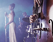 Close-up of a Man Plucking a Double Bass on Stage in a Nightclub and a Female Singer and Saxophonist Standing in the Background