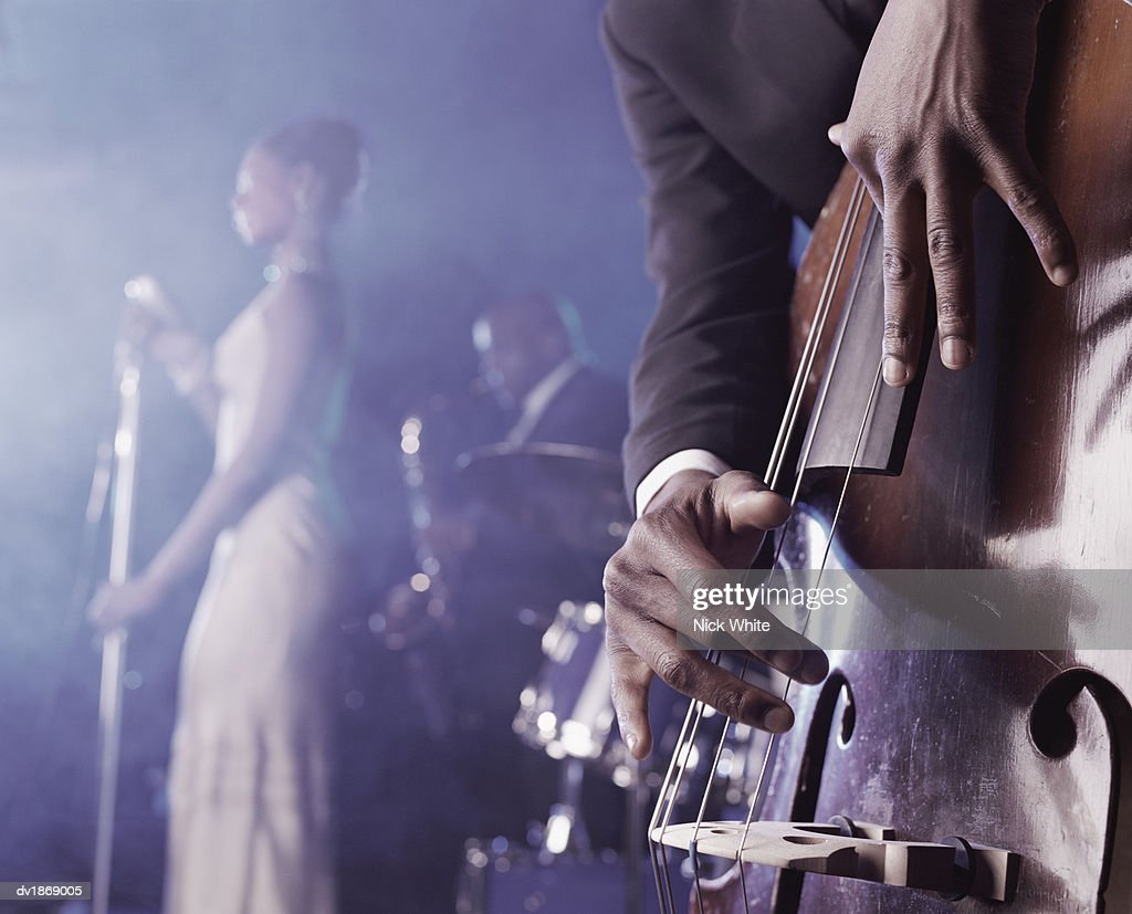 Close-up of a Man Plucking a Double Bass on Stage in a Nightclub and a Female Singer and Saxophonist Standing in the Background : Stock Photo